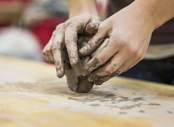 Kädet muotoilevat savea.