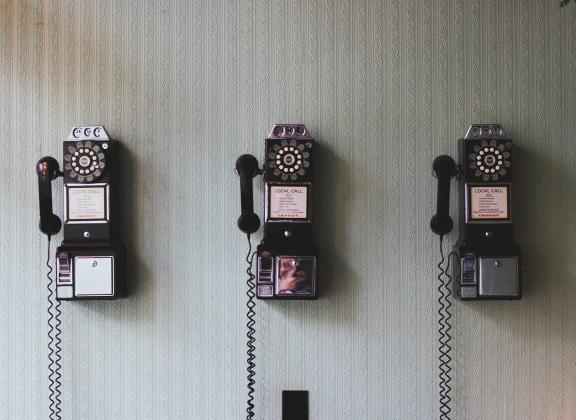 Kolme vanhaa seinäpuhelinta.