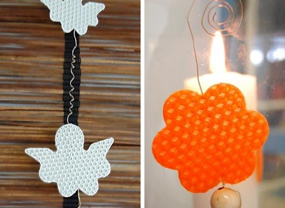 Kuvassa enkelin muotoisia valkoisia koristeita nauhassa ja piparin muotoinen oranssi joulukoriste. Koristeet on valmistettu mehiläisvahasta.