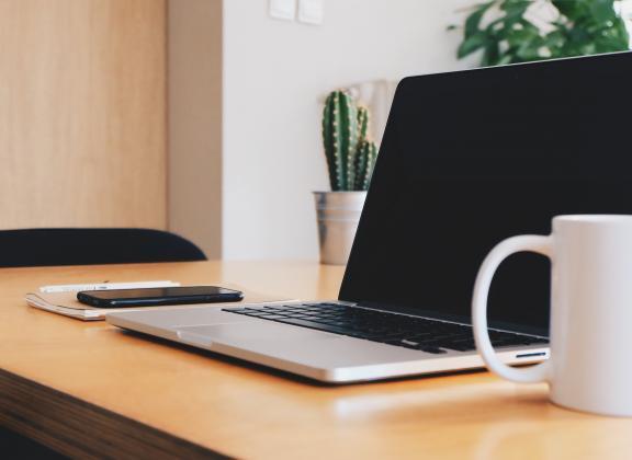 Pöydällä tietokone, puhelin ja kahvikuppi.